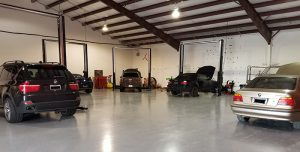 An image of inside Active Euroworks repair shop, with a Mini, 2 BMWs and a Aston Martin being serviced