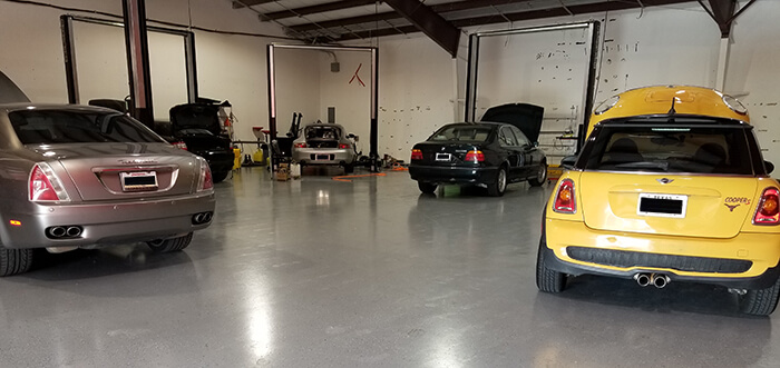 Active Euroworks auto repair shop with a Rolls Royce, Mini, and BMWs being serviced.