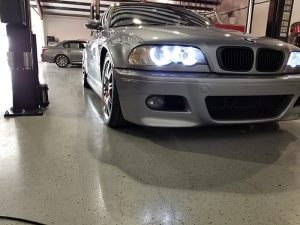 A gray BMW in Active Euroworks repair shop. Xenon lights lit.